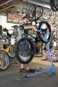 Scott Long posing with a bike in the BikeAthens workshop