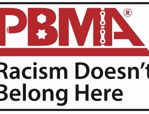 Professional Bicycle Mechanics Association logo with Racism Doesn't Belong Here under it